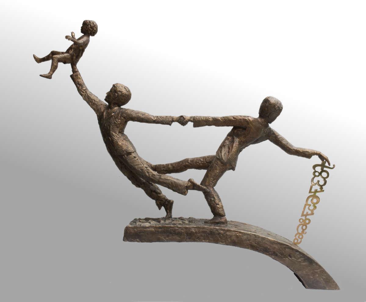 bronsplastiek met twee mannen, waarvan de ene een kind omhooghoudt op zijn rechterhand